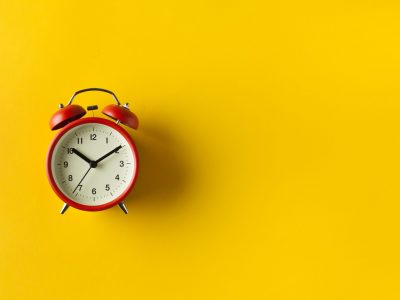 Retro alarm clock on yellow color background